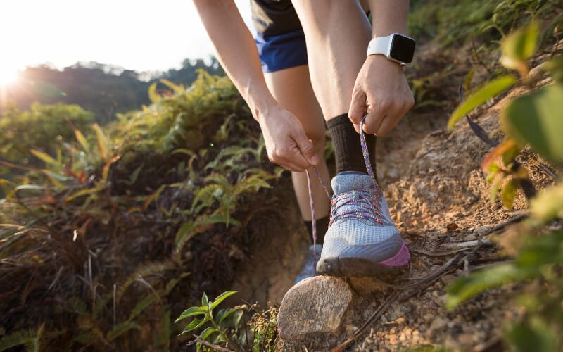 Close up of a woman tying her trail running shoes on a rocky path.