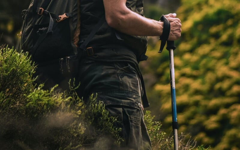 Close up of a man holding a hiking pole during his trek.