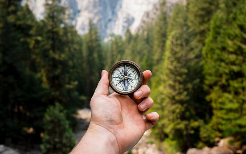 A hand holding a compass on a hike with trees in the background.