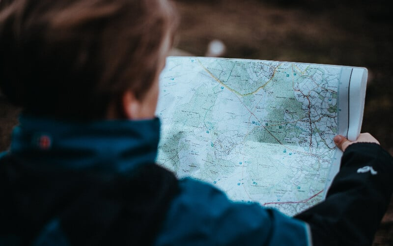 An over-the-shoulder view of a person looking at a hiking map.
