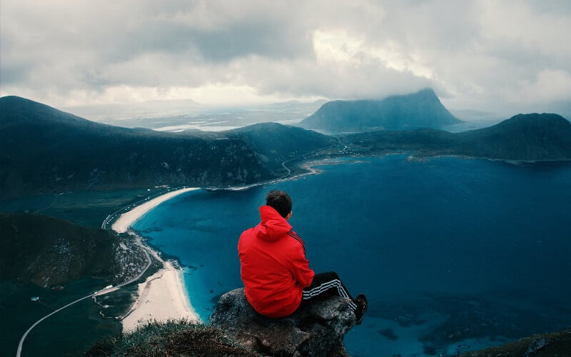 A man wearing a red jacket as an outer layer on a hike, overlooking a body of water and mountains.